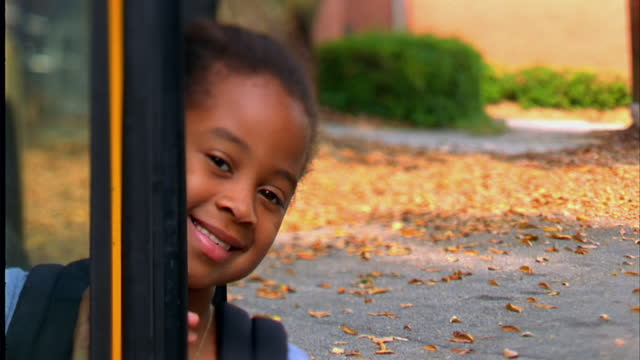 a young girl smiles and peeks around the door of her school bus. - peeking stock videos & royalty-free footage