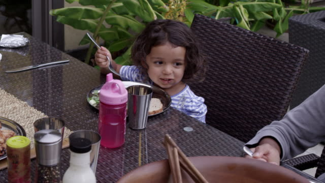 stockvideo's en b-roll-footage met young girl smiles, eats her salad at dinner time in backyard dining table. - tafelmanieren