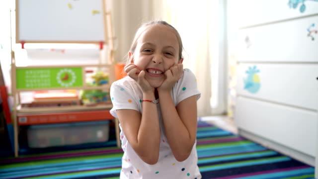 stockvideo's en b-roll-footage met jong meisje glimlachend in de camera en het maken van hart ondertekenen met handen - acteren