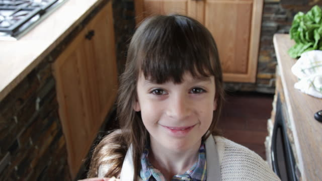 young girl smiling putting on apron in kitchen - apron stock videos & royalty-free footage