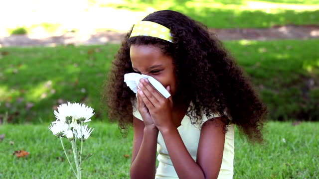 young girl sneezing from hay fever in the park - allergy stock videos & royalty-free footage