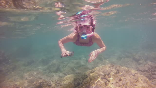 Young girl snorkelling over a shallow reef