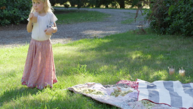 MS Young girl standing in yard by picnic blanket drinking lemonade