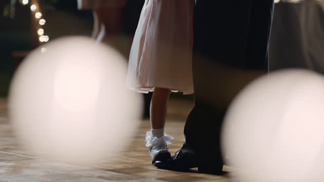 SLO MO. Young girl stands on her father's feet on dance floor at wedding reception.