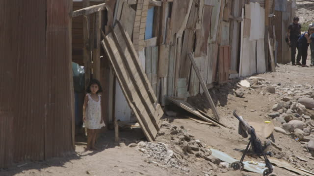 young girl stands outside of low-income house - povertà video stock e b–roll