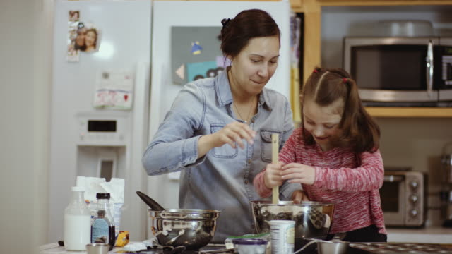 Young girl stirring ingredients while her mother gives instructions