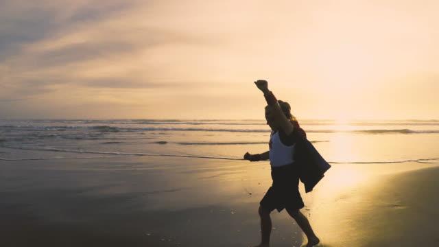 junges mädchen superhero laufen am strand von kalifornien - held stock-videos und b-roll-filmmaterial