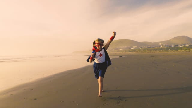 young girl superhero running on california beach - potere femminile video stock e b–roll