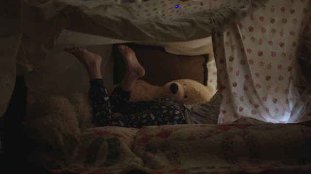 young girl sways her feet inside her blanket fort. - freizeitspiel stock-videos und b-roll-filmmaterial