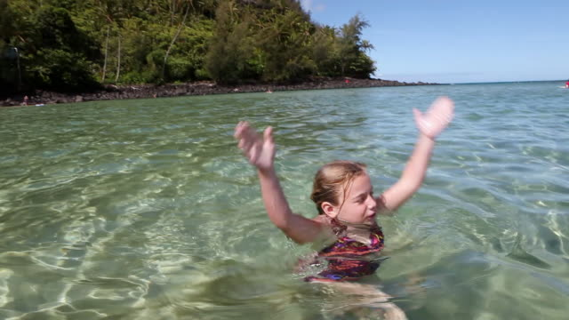 MS Young girl swimming and dancing in ocean / Kauai, Hawaii, United States