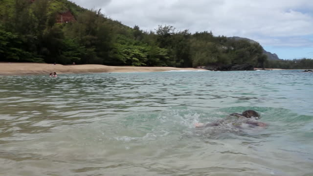 MS PAN Young girl swimming in ocean / Kauai, Hawaii, United States