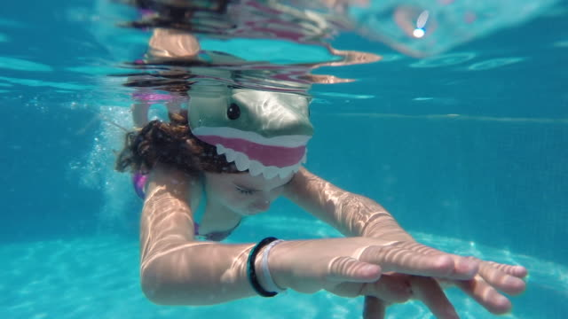 Young girl swimming like a mermaid with a shark hat on in swimming pool