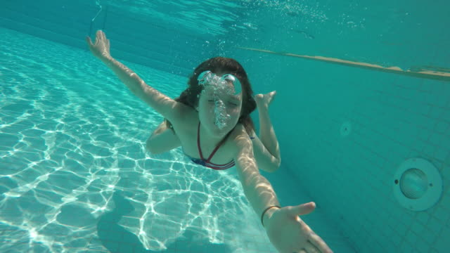 young girl swimming underwater blowing a kiss - badebekleidung stock-videos und b-roll-filmmaterial