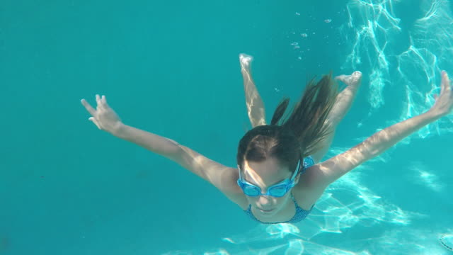 Young girl swimming underwater in pool then coming up for air.