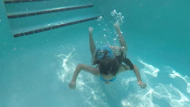 young girl swimming underwater in pool. - one piece swimsuit stock videos and b-roll footage