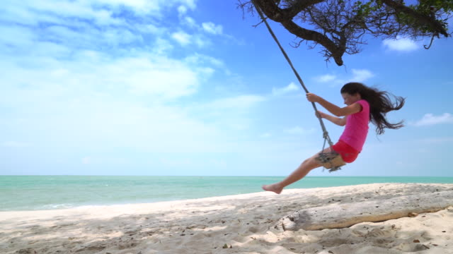 WS SM young girl swinging on a swing by the sea.