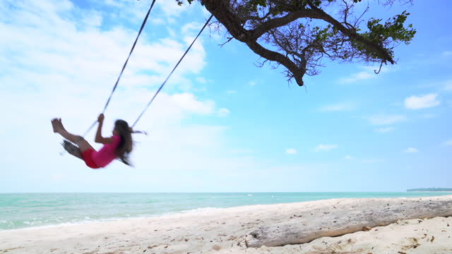 WS young girl swinging on a swing by the sea