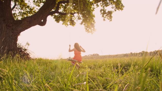若い女性は、ブランコスインギング - ブランコ点の映像素材/bロール