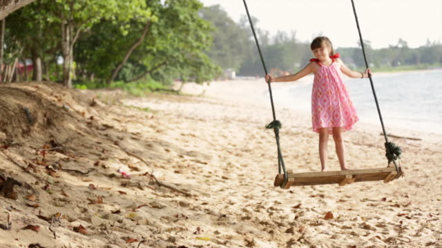 ws young girl swinging on swing next to ocean - swing stock videos & royalty-free footage