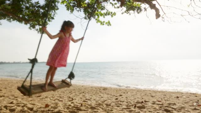 vídeos y material grabado en eventos de stock de ws young girl swinging on swing next to ocean - columpiarse