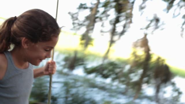 cu young girl swinging on tree swing - 後ろで束ねた髪点の映像素材/bロール