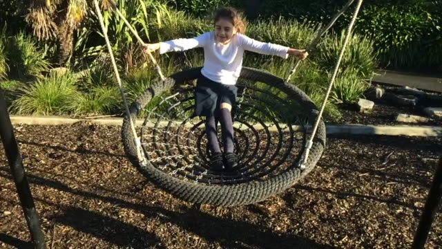 Young Girl Swinging Outdoors on a Spider Net Swing
