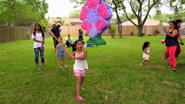 MS Young girl swinging stick at pinata during family birthday party in backyard