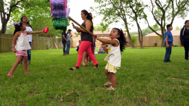 ms young girl swinging stick at pinata during family party in backyard - papier stock videos & royalty-free footage