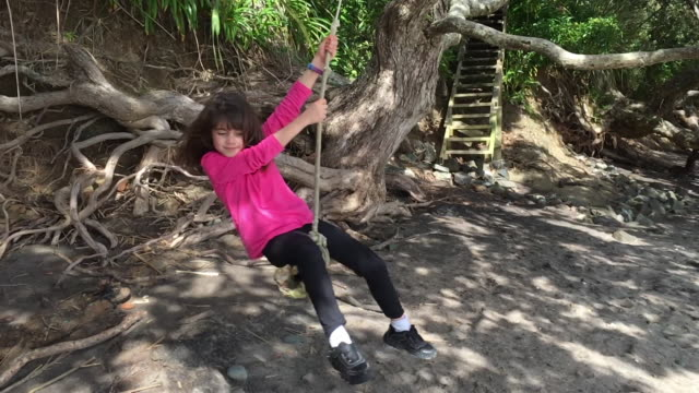 Young girl swings on a tree swing in the beach