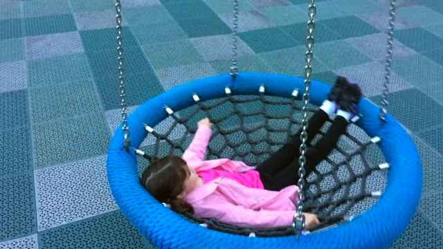 young girl swings on birds nest swing - carefree stock videos & royalty-free footage
