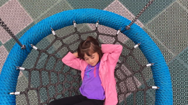 young girl swings on birds nest swing - ブランコ点の映像素材/bロール