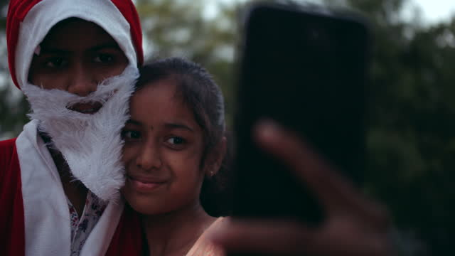 young girl takes a selfie on a smart mobile phone device camera with her brother dressed as santa claus - weihnachtsmütze stock-videos und b-roll-filmmaterial