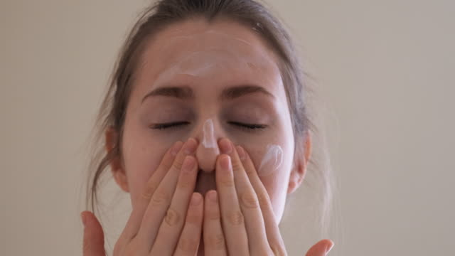 young girl takes care of her face skin. - wrapped in a towel stock videos & royalty-free footage