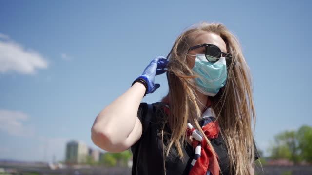 vídeos de stock e filmes b-roll de a young girl takes off her protective mask - remover