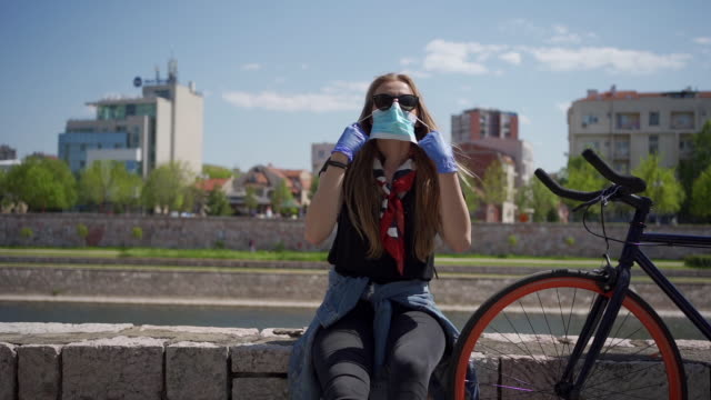 a young girl takes off her protective mask - rimuovere video stock e b–roll