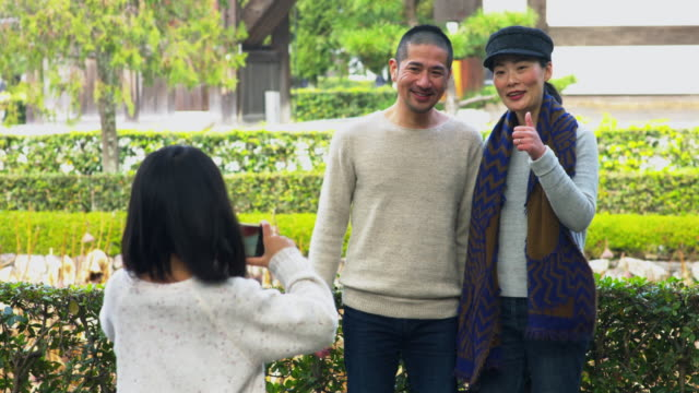 young girl taking a photo of her parents - shrine stock videos & royalty-free footage