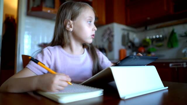 stockvideo's en b-roll-footage met jong meisje het maken van notities in haar notitieblok en e-learning op de tablet. - online leren