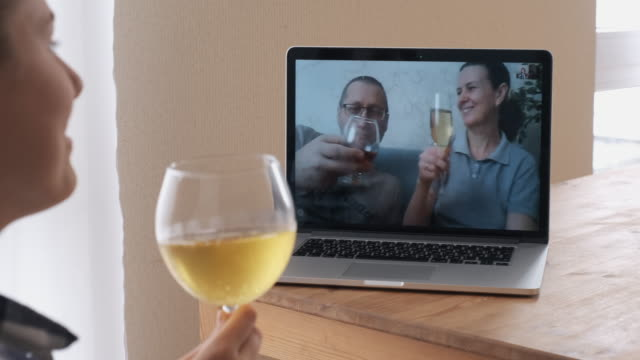 young girl talking in video chat with parents on a laptop, having a drink and having fun. - bicchiere da vino video stock e b–roll