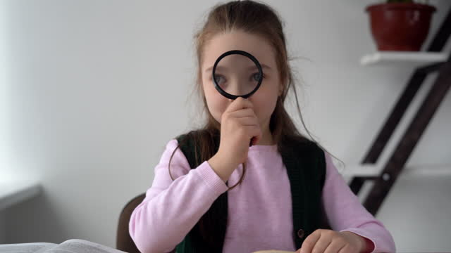 Young girl teenage with a magnifying glass in her hands sits at a desk studies online. Biology lesson for younger students with insect research. The teacher teaches children about distance at home