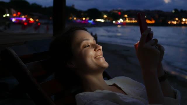 junges mädchen sms am strand - liegen stock-videos und b-roll-filmmaterial