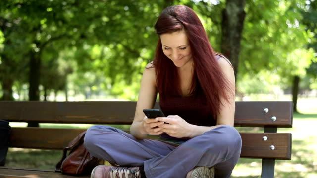 若い女の子まさに本物のスマートフォン - ベンチ点の映像素材/bロール