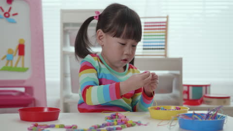 young girl threading beads onto string craft - one girl only stock videos & royalty-free footage