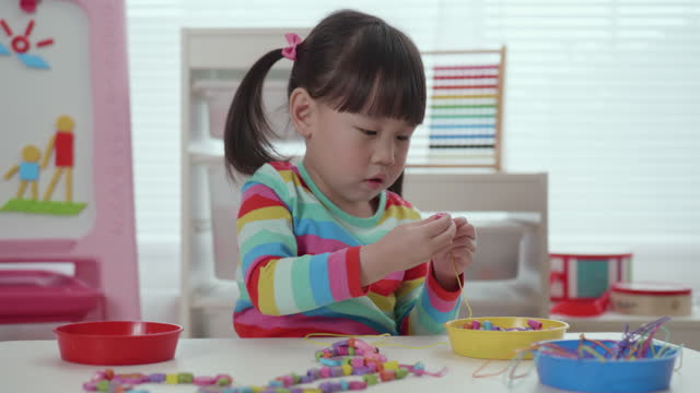 young girl threading beads onto string craft - preschool child stock videos & royalty-free footage