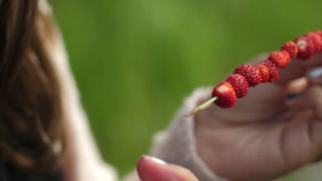 junge mädchen einfädeln wilde erdbeeren smultron auf gras stroh - menschlicher finger stock-videos und b-roll-filmmaterial