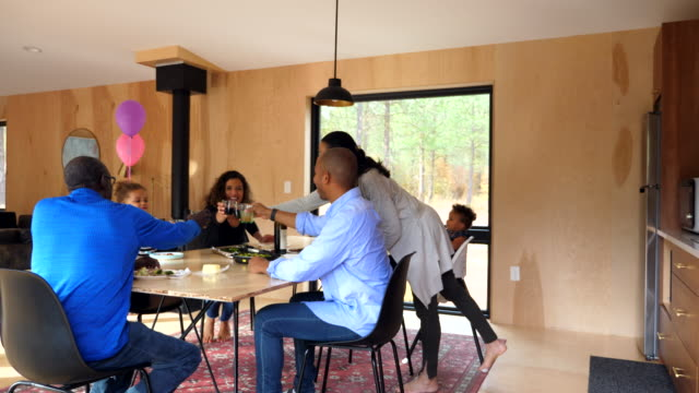 vidéos et rushes de ms young girl toasting with family during dinner at kitchen table - prendre son repas