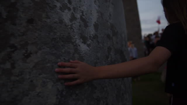 vídeos y material grabado en eventos de stock de young girl trails her hand along a stone at stonehenge. - solsticio de verano