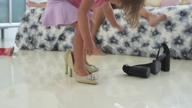 young girl trying on high heels. - verkleidung kleidung stock-videos und b-roll-filmmaterial