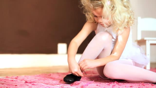 Young girl tying her shoelace