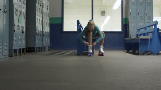 vídeos de stock e filmes b-roll de young girl tying shoelaces on ice skates. - patinagem no gelo