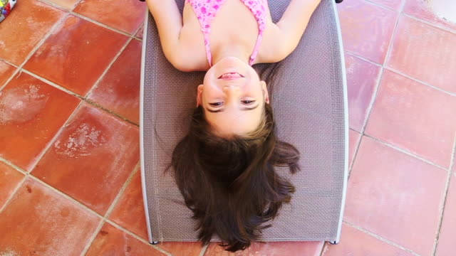 young girl upside down looking at camera lying on the backyard home on summer doing funny faces - upside down stock videos and b-roll footage